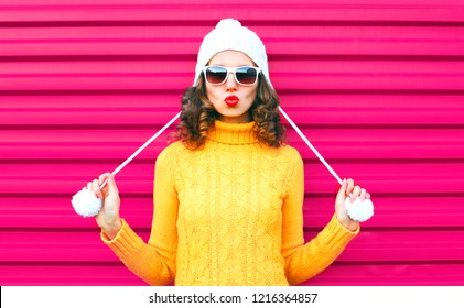 Funny girl blowing red lips makes air kiss wearing colorful knitted yellow sweater hat over pink background