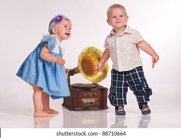 Funny girl and a boy dancing near the gramophone.