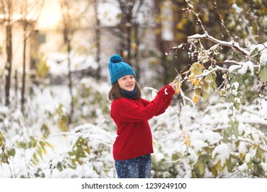 funny girl child in colorful clothes, red sweater plays with the first snow outdoor.