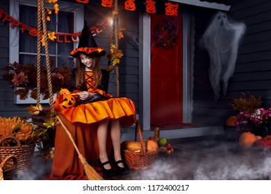 Funny girl child kid in halloween witch costume with black hat and orange pumpkins basket with spooky face for candies and sweets sitting on swing ready for celebration autumn holiday halloween.