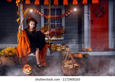 Funny girl child kid in halloween witch costume with black hat and orange pumpkins basket with spooky face for candies and sweets sitting on yard swing ready for celebration autumn holiday halloween.