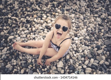 funny girl child shows tongue on the beach in a striped swimsuit and sunglasses, glasses in the shape of hearts. Pebble beach.