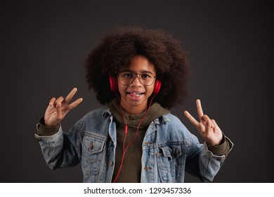 Funny girl in denim jacket showing peace signs against dark background