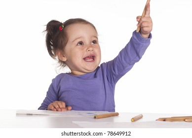 funny girl drawing at the table on a white