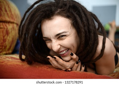 funny girl with dreadlocks laughs and wrinkles her nose