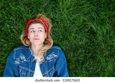 Funny girl dressed in a denim jacket lying on a green lawn and looking sideways on copyspace. Top view.