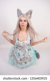 funny girl with fluffy fur cat ears stands in kitchen apron on her knees and shows anime ahegao face on white background in Studio
