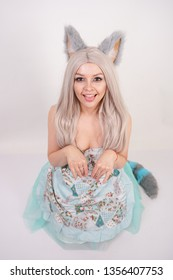 funny girl with fluffy fur cat ears stands in a kitchen apron on her knees and serves as a kitty in a role-playing sexy game on a white background in the Studio