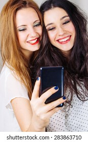 Funny girl friends taking selfies with a mobile