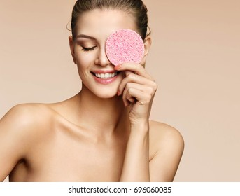 Funny girl holding pink sponge near her face. Portrait of young girl on beige background. Youth and skin care concept