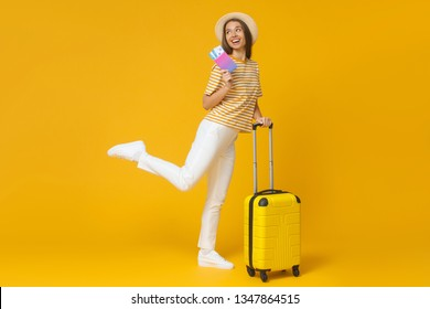 Funny girl jumping, holding suitcase and passport with flight tickets, isolated on yellow background