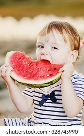 Funny girl kid at countryside eating juicy watermelon.