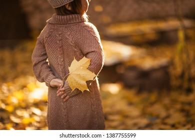Funny girl in a knitted sweater and a crown with gold leaves, very evening and soft light
