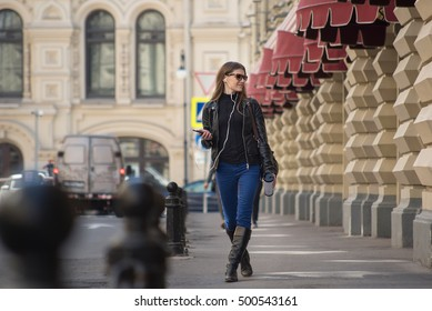 Funny girl listening to the music with earphones from a smart phone and dancing with an urban background