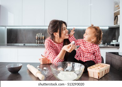 Funny girl with mom on kitchen. in dress. so cune family