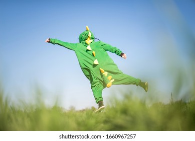 Funny girl in pajamas costume dragon flies in the pose of Superman horizon in the field