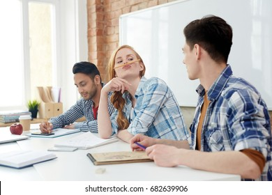 Funny girl with pencil between her upper lip and nose looking at one of her groupmates in classroom