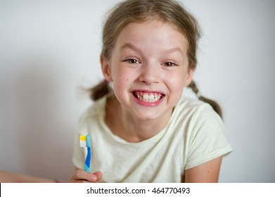 Funny girl with pigtails brushing his teeth. She shows their clean white teeth with a cheerful smile.
