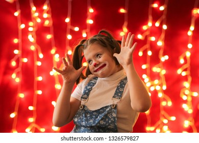 Funny girl with funny pigtails drawn by a clown on a red background with lights. Concept childhood, artistry, circus and theater. April Fool's Day