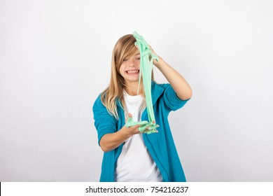 Funny girl playing with green slime looks like gunk