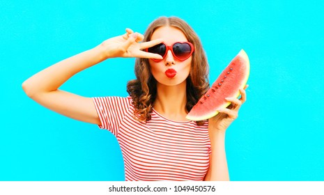 Funny girl portrait woman is holding slice of watermelon and blowing lips over a colorful blue background