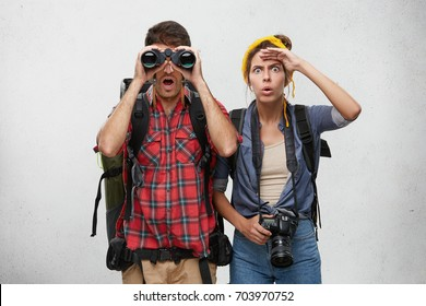 Funny girl with professional camera keeping hand on her forehead and looking into distance, her handsome bearded boyfriend with mouth dropped open viewing something astonishing through binocular