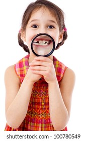 Funny girl showing teeth through a magnifying glass, isolated on white