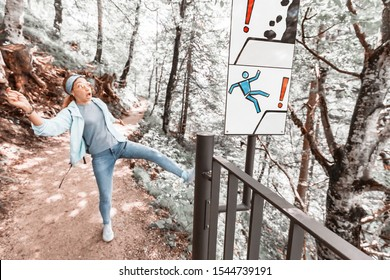 Funny girl slipped on the slippery slope of a Hiking trail in the mountains near the sign. Risk and safety concept