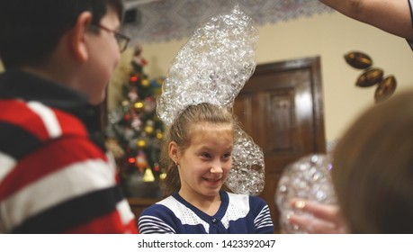 Funny girl with the soap bubbles on her head in a cafe among friends on the birhday