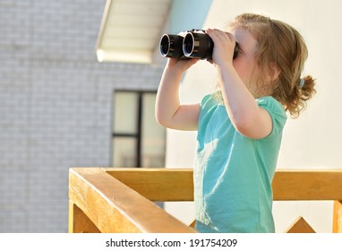 Funny girl standing on a balcony of a private house with binoculars