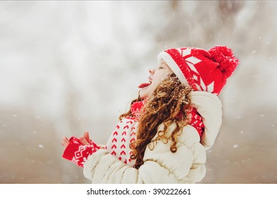 Funny girl stuck out her tongue and catches snowflakes. Happy childhood. Traveling. Christmas concept.