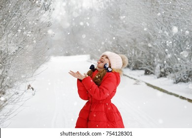 Funny girl stuck out her tongue and catches snowflakes. Happy childhood, Christmas concept.