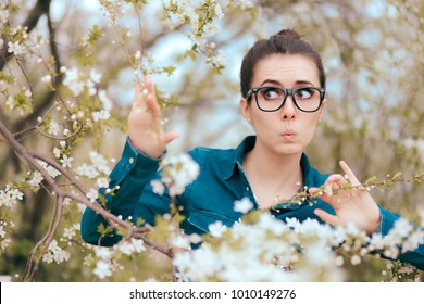 Funny Girl Surrounded by Blossoming Trees Afraid of Allergies. Circumspect woman analyzing effects of spring blooming nature on her health