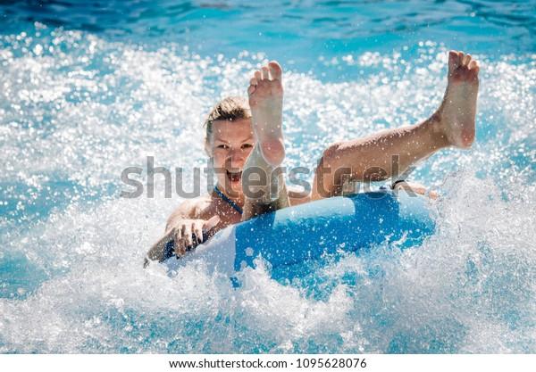 Das sonnige Mädchen fährt schnell mit Wasser auf einem schwimmenden Wasser. Sommerurlaub mit Wasserpark Konzept.