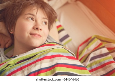 Funny girl teenager lying in bed under a striped colored blanket. Toned
