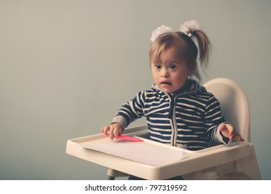 funny girl toddler with Down syndrome with gay emotions draws, lifestyle, selective focus and toning
