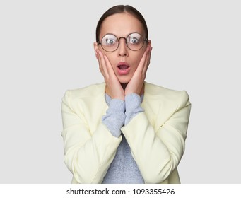 funny girl wearing spectacles. Shocked woman isolated on grey