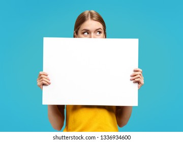 Funny girl with white empty poster looking away on blue background. Copy space for your text.