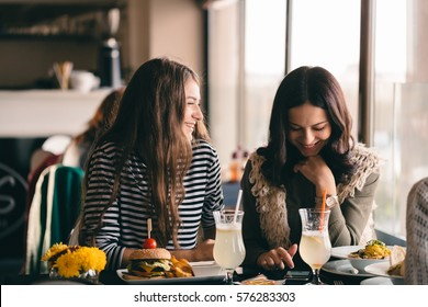 Funny girls meeting up for lunch break to eat delicious food and have a break. Girls fooling around and experiencing new hair-dos thinking about make-over or making change in style.