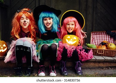 Funny girls showing tongues and looking at camera on Halloween night