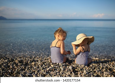 Funny girls sisters in striped swimsuits with a hat on a pebble beach by the sea, the baby plays with a sister on the beach. Concept vacation with children, children and the sea. Turkey Kemer