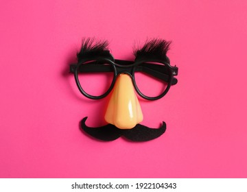Funny glasses on pink background, top view