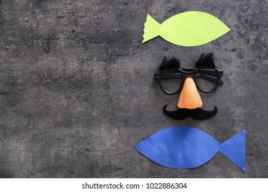 Funny glasses and paper fish on grey background. April fool's day celebration