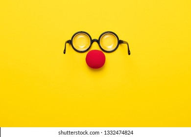 Funny glasses, a red clown nose and tie on a colored background, like a face. Flat lay. Funny costume for the holidays. Anonymous concept.