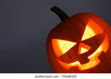 Funny glowing Halloween Pumpkin on gray background