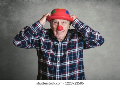 funny grandfather with hat and clown nose on gray background