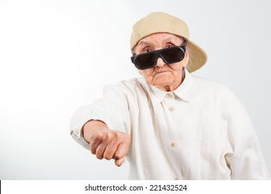 Funny grandma's studio portrait  wearing eyeglasses and baseball cap who kicks with  her fist , isolated on white