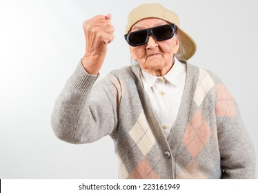 Funny grandma's studio portrait  wearing eyeglasses and baseball cap, who hist with her fist  isolated on white