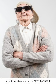 Funny grandma's studio portrait  wearing eyeglasses and baseball cap, who stands for her right,  isolated on white