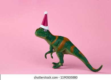 funny green dinosaur toy in little santa claus hat  on pastel pink background